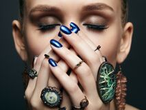 Young woman with eyes closed and many bijouterie rings with stones on fingers