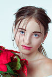 Beauty portrait of young girl. Morning image with the effect of wet face. The girl in the hands holding a red flower. Royalty Free Stock Image