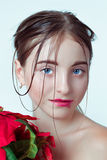 Beauty portrait of young girl. Morning image with the effect of wet face. The girl in the hands holding a red flower. Royalty Free Stock Photos