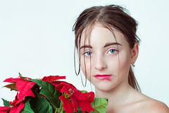 Beauty portrait of young girl. Morning image with the effect of wet face. The girl in the hands holding a red flower. Stock Photography