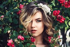 Beauty portrait of young green-eyed girl between roses. royalty free stock images