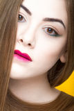 Beauty portrait of young white girl with creative makeup and hair isolated on yellow background. Stock Photos