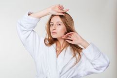 Beauty portrait of a young woman in bathrobe. Standing isolated on a white background Stock Photos