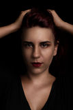 Beauty portrait of a young woman on black. Beautiful red haired young woman holding her hair on black background Royalty Free Stock Photos