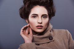 Beauty portrait. Young woman in a coat with a hairstyle and makeup is looking at camera, on a dark background stock photos