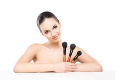 Beauty portrait of a young woman holding makeup brushes Stock Photo