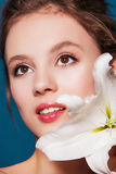 Beauty portrait of young woman with the lily flower on blue Stock Images