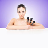 Beauty portrait of a young woman with makeup brushes. Beauty portrait of young, attractive, fresh, healthy and natural woman with a makeup brushes and a blank royalty free stock image