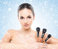 Beauty portrait of a young woman with makeup brushes Royalty Free Stock Photography