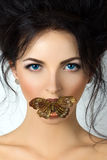 Beauty portrait of young woman with mouth covered with butterfly Stock Photo