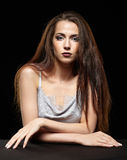 Beauty portrait of young woman sit at the black table. Brunette. Girl with long hair and evening female makeup on dark background Stock Photography