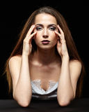 Beauty portrait of young woman sit at the black table. Brunette. Girl with long hair and evening female makeup on dark background stock photo