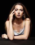 Beauty portrait of young woman sit at the black table. Brunette. Girl with long hair and evening female makeup on dark background stock photos