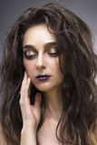 Beauty portrait of the young woman with a vanguard make-up. Beauty portrait of the young woman in a with a vanguard make-up and a flowing hair on a gray Royalty Free Stock Photography
