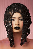In black crown. Beauty portrait of young woman wearing crown head piece with creative makeup Stock Image
