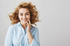 Beauty and positive emotions concept. Indoor shot of sensual emotive young woman in blue blouse with short stylish curly. Hairstyle, standing over gray royalty free stock image