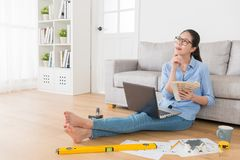 Beauty pretty woman holding color list tool. Thinking new house plan when she sitting on living room floor using laptop working royalty free stock images