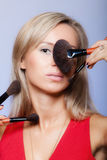 Beauty procedures, woman holds make-up brushes near face. Royalty Free Stock Image