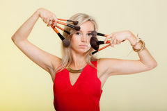 Beauty procedures, woman holds make-up brushes near face. Royalty Free Stock Photography