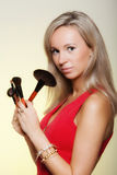Beauty procedures, woman holds make-up brushes near face. Royalty Free Stock Photo