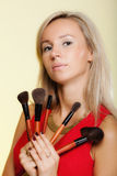 Beauty procedures, woman holds make-up brushes near face. Stock Photo