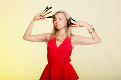 Beauty procedures, woman holds make-up brushes near face. Royalty Free Stock Images