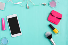 Beauty products, everyday make-up and mobile on blue Stock Photos