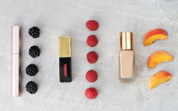 Beauty products, everyday makeup with berries and peach for color comparison. copy space Royalty Free Stock Photography