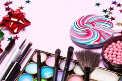 Beauty products for holiday party makeup. Holiday party makeup. Beauty products with make-up brushes, lollipop, confetti and gift wrap bows Stock Photos