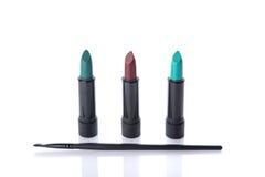 Beauty products, makeup brush and three lipsticks Stock Photo