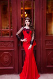 Beauty queen in a red dress with long hair and a tiara on her head. Beautiful young girl in a red evening long dress. The beauty queen in a red dress with long Royalty Free Stock Image