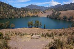 The Beauty of Ranu Kumbolo. Some climbers walk on hiking trails which located in the edge of the beautiful lake inside Bromo Tengger Semeru National Park royalty free stock photos