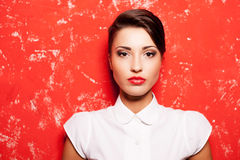 Beauty on red. Beautiful young short hair woman in white shirt posing against red background Royalty Free Stock Image