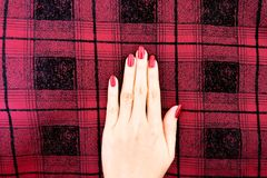 Beauty Red Manicure Nail with Gel Polish. Woman Hand with Red Nails on the Red Scot Fabric Background. Great for Any Use Stock Photos