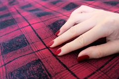 Beauty Red Manicure Nail with Gel Polish. Woman Hand with Red Nails on the Red Scot Fabric Background. Great for Any Use Royalty Free Stock Image