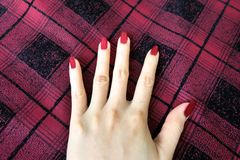 Beauty Red Manicure Nail with Gel Polish. Woman Hand with Red Nails on the Red Scot Fabric Background. Great for Any Use Royalty Free Stock Photo