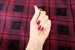 Beauty Red Manicure Nail with Gel Polish. Woman Hand with Red Nails on the Red Scot Fabric Background. Great for Any Use Stock Image