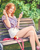 Beauty redhead woman primping with mirror in the Stock Photography