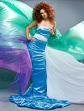 Beauty redheaded girl in fashion dress. On gray background Stock Photo