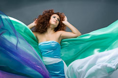 Beauty redheaded girl in fashion dress. On gray background Royalty Free Stock Photo