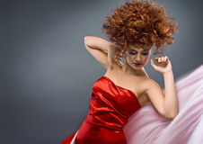 Beauty redheaded girl in fashion dress. On gray background Stock Photography