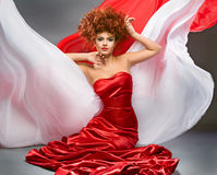 Beauty redheaded girl in fashion dress. On gray background royalty free stock image