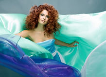 Beauty redheaded girl in fashion dress. On gray background royalty free stock photos
