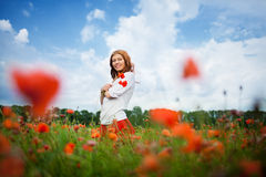 Beauty redheaded woman. In poppy field Royalty Free Stock Image