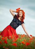Beauty redheaded woman. In poppy field Stock Photos