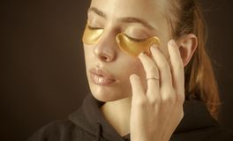 Beauty and refresh, collagen mask. Under eyes gold color from wrinkles on face of woman, skincare and spa, cosmetics stock photo