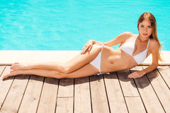 Beauty relaxing poolside. Stock Photos