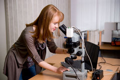 Beauty researcher looking through microscope in laboratory Royalty Free Stock Photo