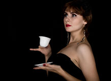 Beauty retro female model with professional makeup, drinking coffee or tea. fashion vintage woman on a dark background Stock Images