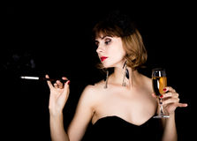 Beauty retro female model with professional makeup holding mouthpiece and glass of champagne. fashion vintage woman on a Royalty Free Stock Photography